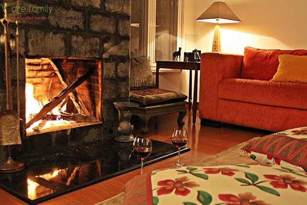 Warm glow from the lit fireplace in the living space on ground level with earthy furnishings