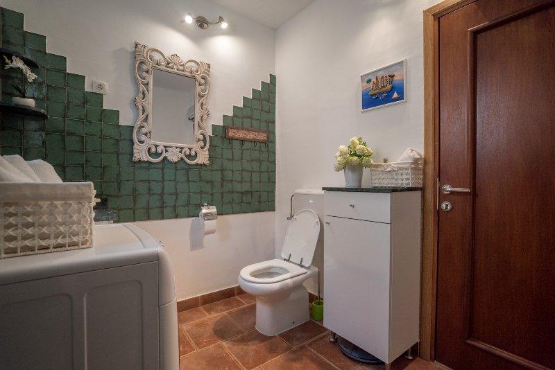 Bagno con doccia e lavatrice al piano terra