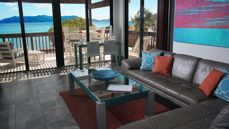 Beautiful, spacious living room has 2 sets of glass doors letting the ocean air and sounds inside