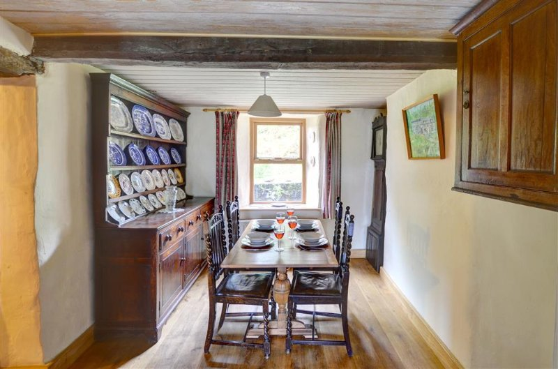 The formal dining room, open to the kitchen, has a substantial Welsh dresser, and traditional dark oak dining table and chairs
