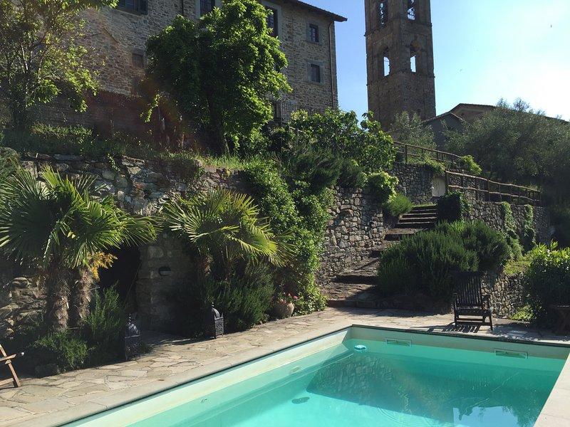 Vista de la villa y de la torre de la iglesia de la terraza de la piscina.