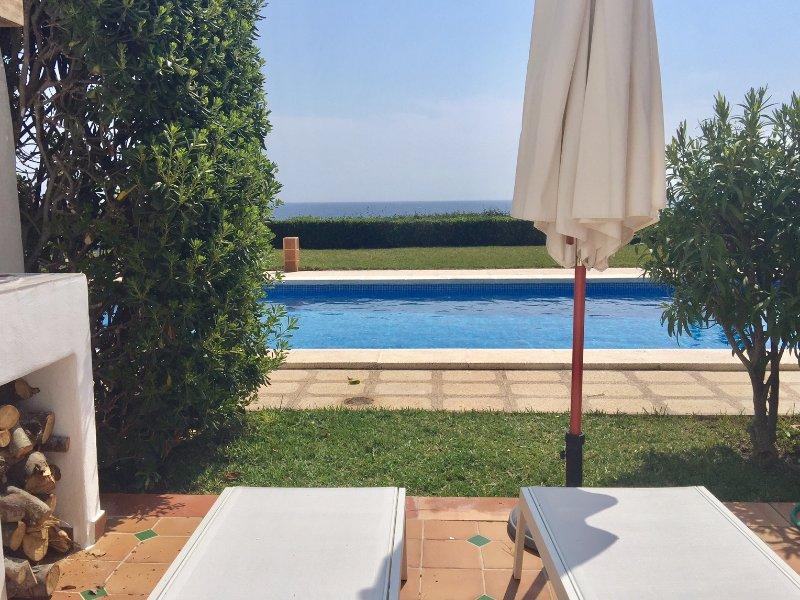 Apartamento con jardín y piscina frente al mar, holiday rental in Cala Marcal
