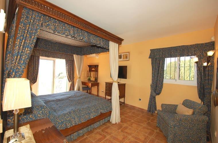 La chambre principale avec lit à baldaquin et un grand espace, avec terrasse privée menant au large, il