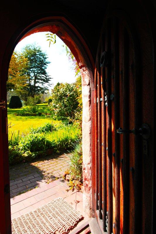 La porta d'ingresso cappella e una vetrata occupano gli originali archi a sesto acuto gotici medievali.