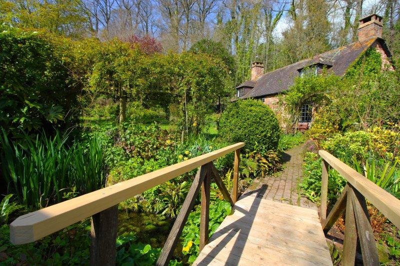 Al di là dei ponti in giardino, un cancello sul retro si apre su un sentiero pubblico su terreni agricoli.