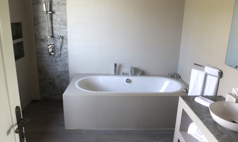 Badkamer 3 met ligbad voorzien van rand breed genoeg voor waxinelichtjes en een glas voor maximaal comfort