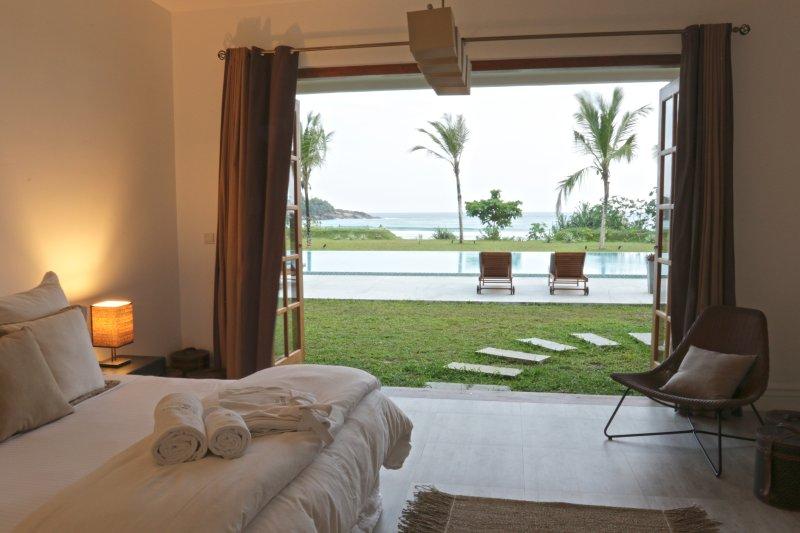 Slaapkamer 1 toegang tot de tuin, zwembad en het strand door prachtige bi-vouwdeuren