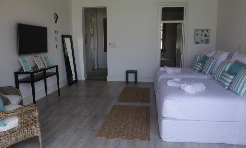 Slaapkamer 2 uitgerust met 2 queen bedden, TV, badkamer en toegang tot het balkon