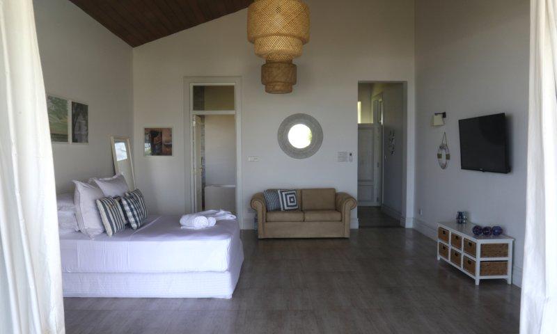 Slaapkamer 3 met Queen bed en een bank, een televisie en een eigen badkamer. Toegang tot balkon en tuinmeubilair