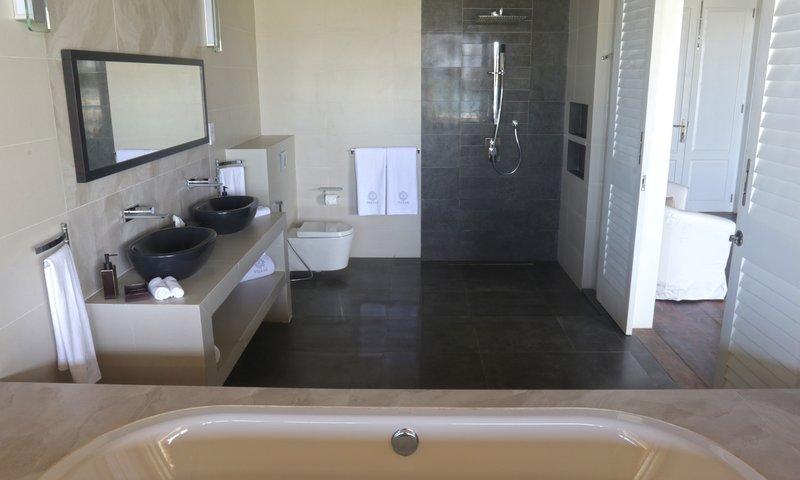 spectaculaire grote badkamer met regendouche en voorzien van een ligbad kijkt uit naar de oceaan