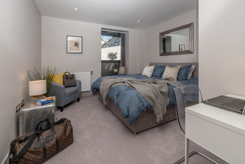 Luxury master bedroom with quality super king size bed with a view of tranquil garden patio.