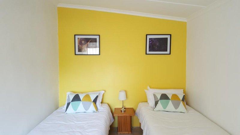 Segundo dormitorio con dos camas y una cómoda.