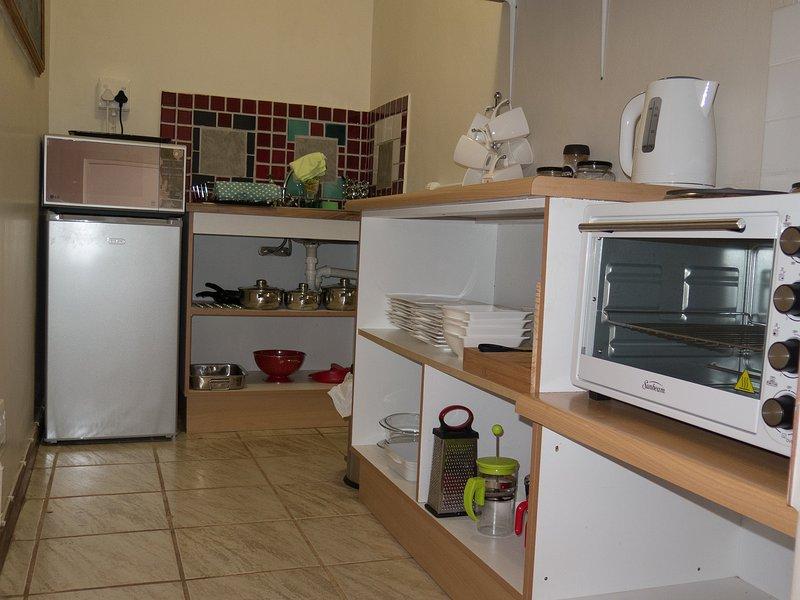 Kitchen with stove, microwave, fridge/freezer, kettle, toaster, pots & pans, crockery, glasses etc
