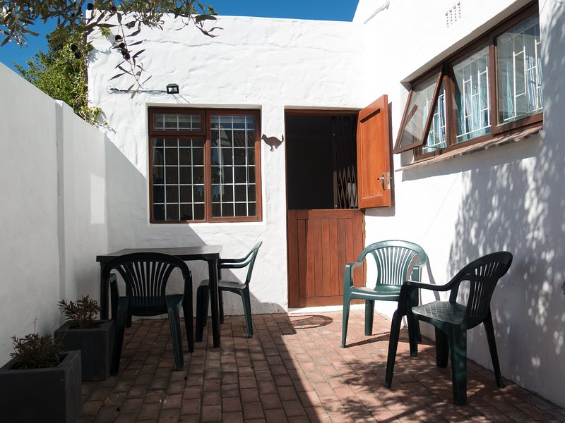 Private courtyard with seating for 4 people and braai (barbeque) with utensils.