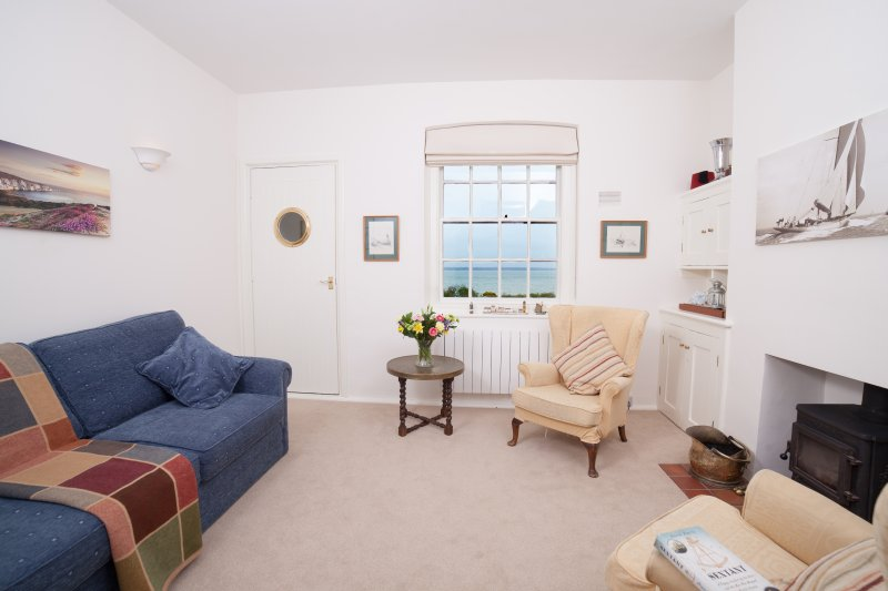 The living room in Serendipity have fabulous views of the sea, and a log burning stove