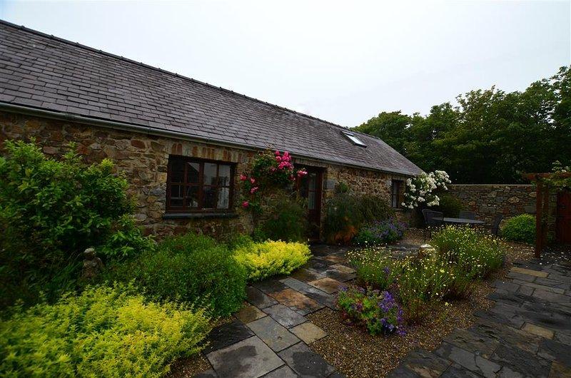 Extérieur de l'avant de la propriété, le patio à la porte principale avec des plantes et des arbustes