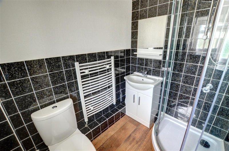 De compacte badkamer is modern met een toilet, wastafel wastafel en douchecabine