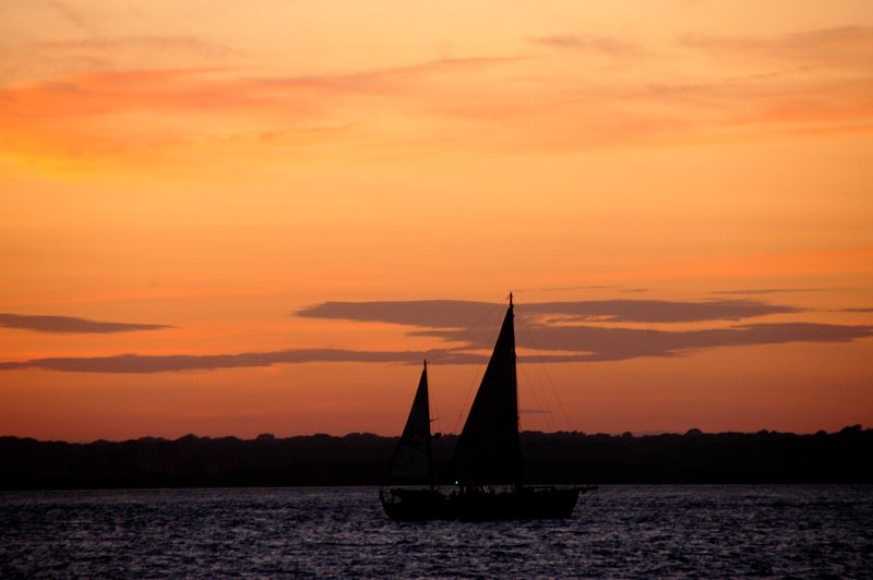 A yacht sailing past the cottage at sunset