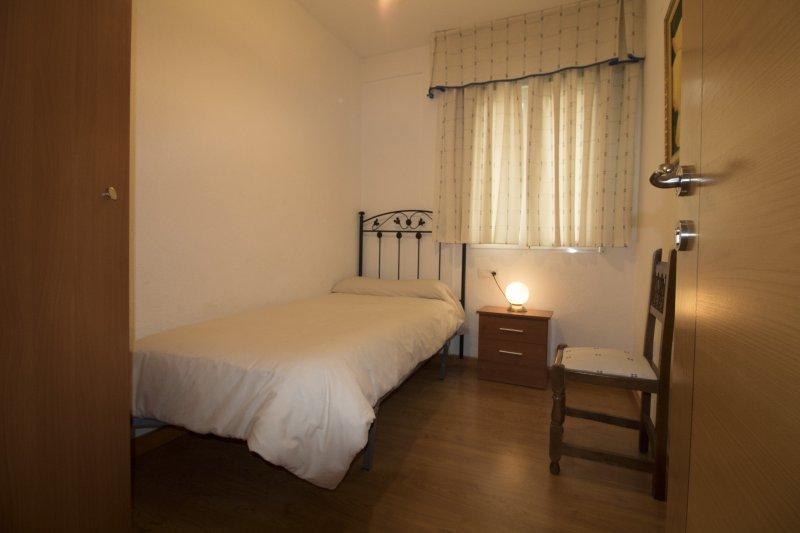 Dormitorio individual, con armario, mesita de noche y emisor térmico programable.