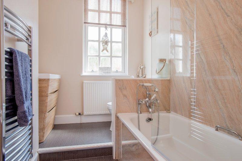 O banheiro do térreo tem uma banheira de aço revestido e um chuveiro duplo.