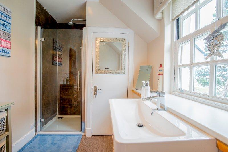 A casa de banho no andar de cima tem um grande chuveiro duplo.