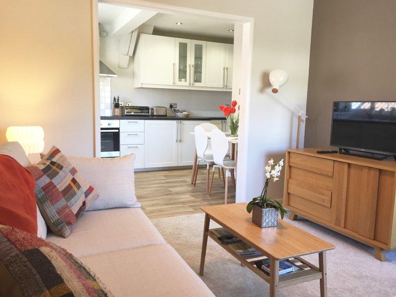 Stilvolle Wohnzimmer mit Smart TV und Chaise Sofa-Bett mit Blick Amerikanische Küche zu öffnen