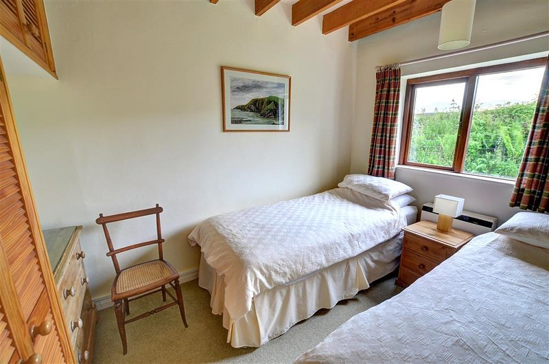 The second bedroom is simply furnished with twin beds and neutral soft furnshings