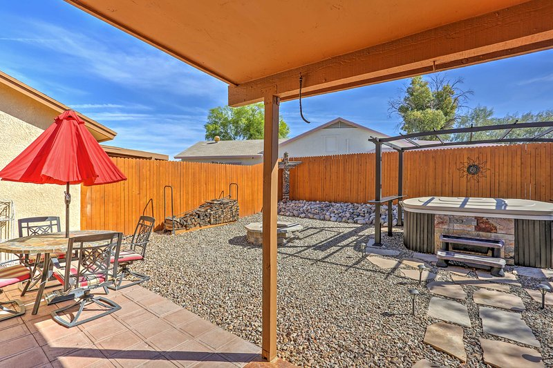 The fenced-in yard features a dining area, grill, totem poles and solar lighting.