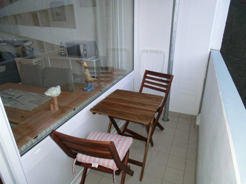 Balcon avec des chaises en bois confortables