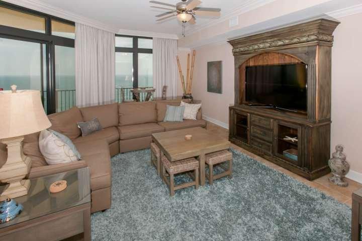 Sala de estar con televisor de pantalla plana grande, mesa de centro con 4 taburetes y ventilador de techo
