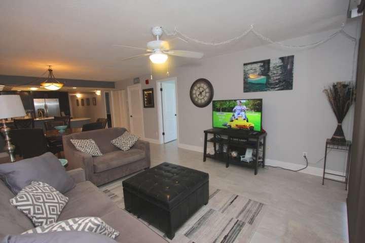 sala de estar con TV de pantalla plana y sofá cama.