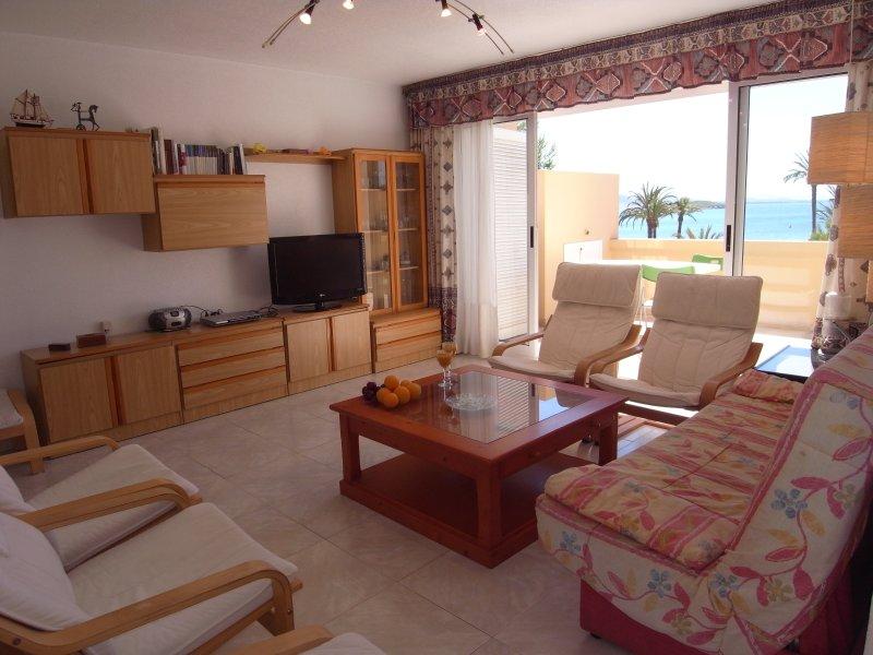 salone con divano a tre posti, quattro poltrone, armadi e terrazza con vista sul Mar Menor