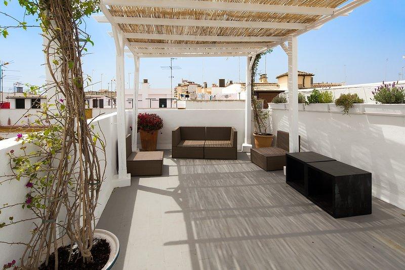 La terrasse dispose d'une aire de repos avec une atmosphère accueillante, pergola remplie de plantes et des sièges en plein air.