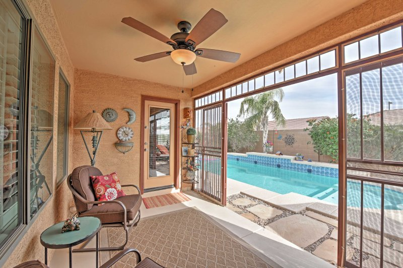 Relax poolside in the home's gorgeous sun porch!