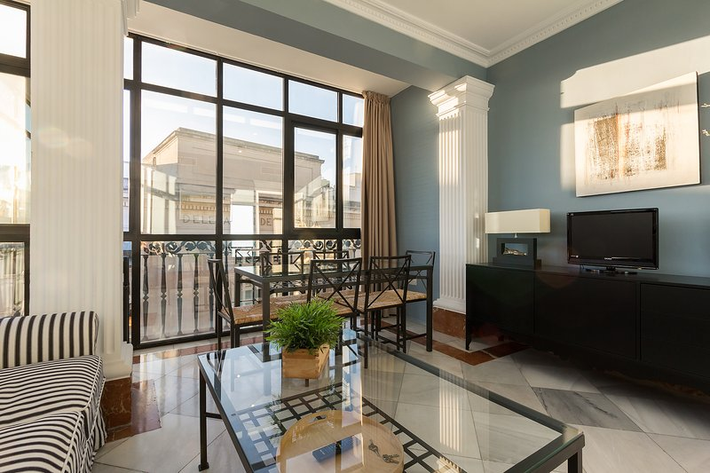 Bright living room with large glass walls and views over Seville's historic centre.