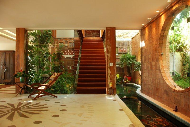 Vestíbulo de entrada nivel principal, lago con peces koi japonés a derecha, escalera rodeada de jardín