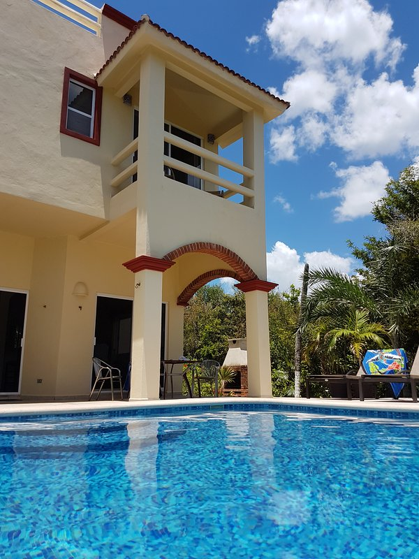 View of the covered pool terrace and the orange bedroom balcony, from the pool.