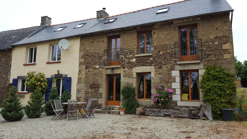 Front of cottage, with wooden dining table and chairs, plus plenty of parking space