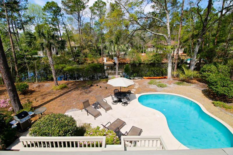 View of pool, lagoon, grill, and dock from master bedroom balcony