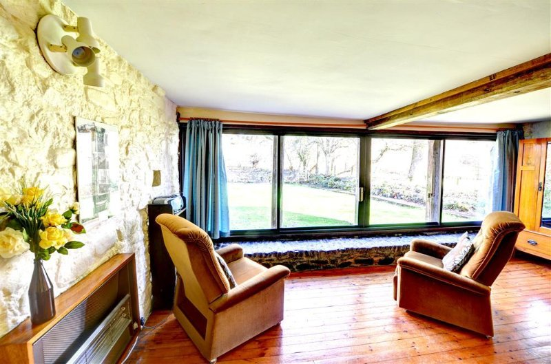 The two comfortable armchairs look out through the picture windows over the lawned garden