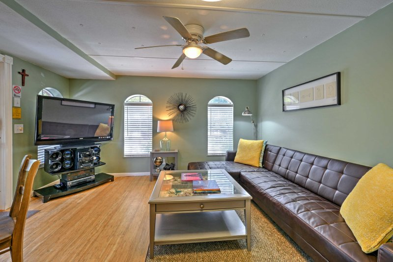 Living room has a flat screen TV with Roku streaming device leather sectional for relaxing