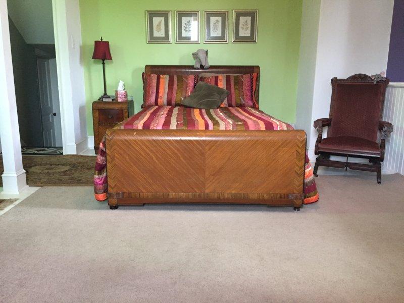 Habitación con cama de matrimonio, tocador, cómoda, silla, mesita de noche y dos armarios.