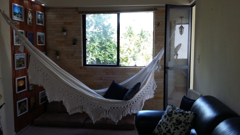 Living room with lounge and a hammock for relaxing after the beach.