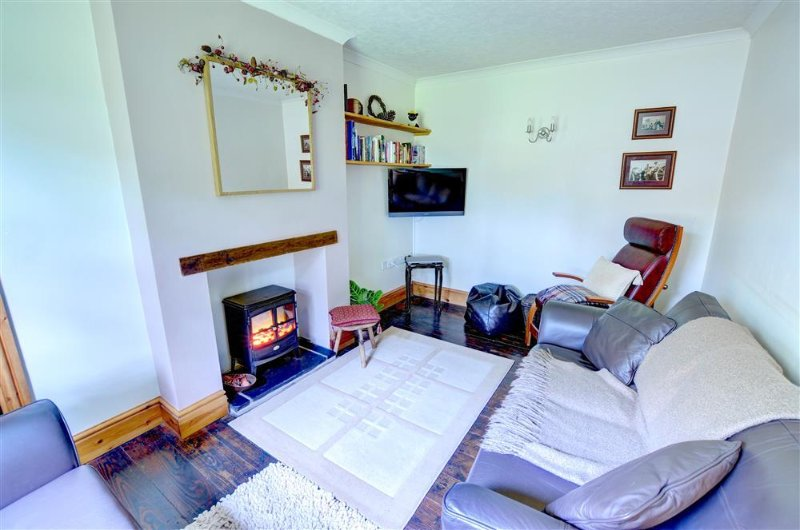 The sitting room has an electric woodburner, creating a warm cosy space