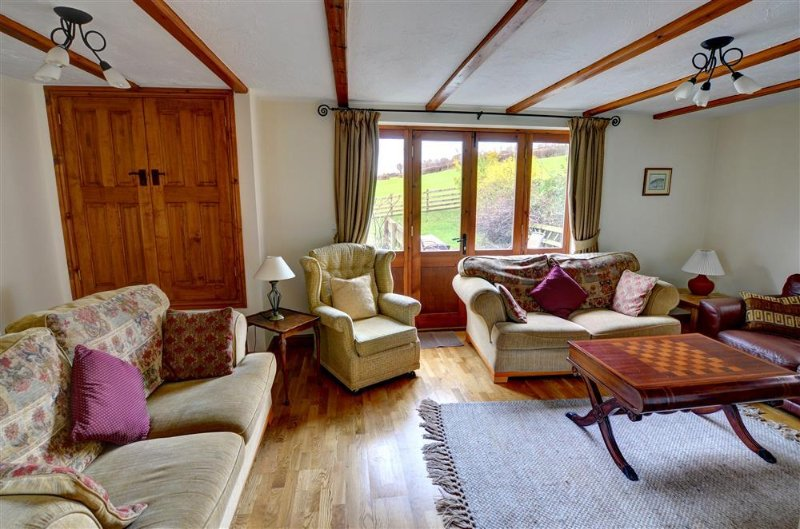The sitting room has glazed doors onto the patio overlooking open countryside