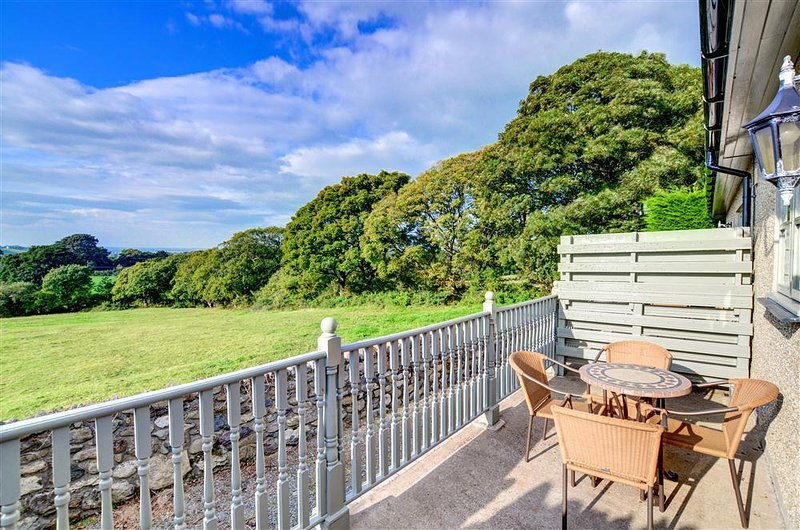 The balconied patio to the rear has patio furniture and overlooks open countryside