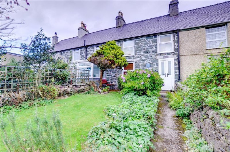 A mid-terraced stone cottage in the village of Fron, in the Snowdonia mountains above Caernarfon