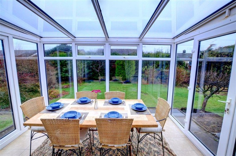 The conservatory is furnished for dining, with a table and six chairs