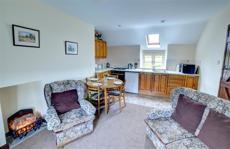 Open-plan living accommodation with fitted kitchen at one end, dining and three piece suite