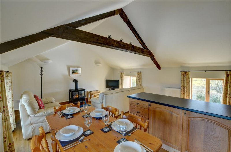 The living room has a woodburning stove and a hand-made oak fitted kitchen